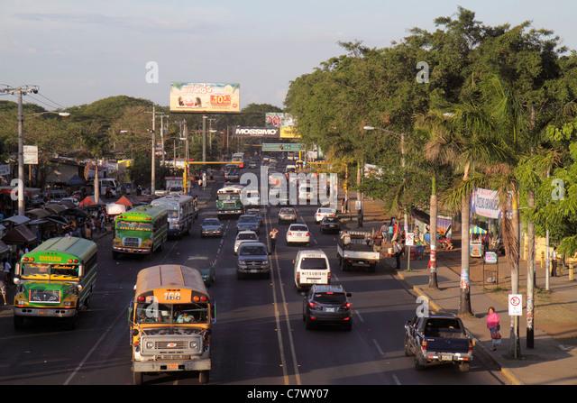 Managua Nicaragua Pista de la Resistencia street scene large avenue bus truck car traffic pedestrian tree lined - Stock Image