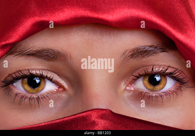 Close up of a pair of beautiful female brown eyes framed by a red silk veil - Stock Image