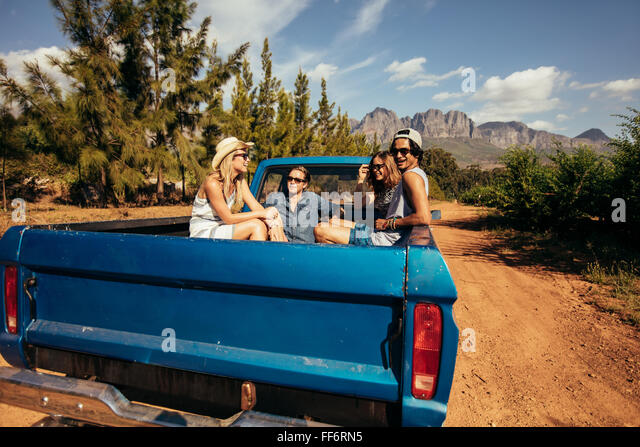 Group of friends sitting at the back of a pick up car. Young men and women going on a road trip in nature. - Stock Image