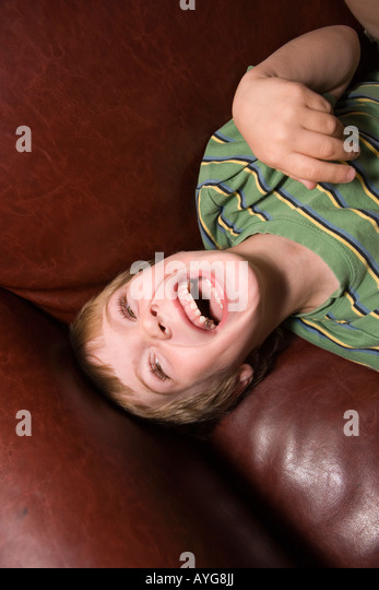 five year old boy laughing on sofa at home - Stock-Bilder