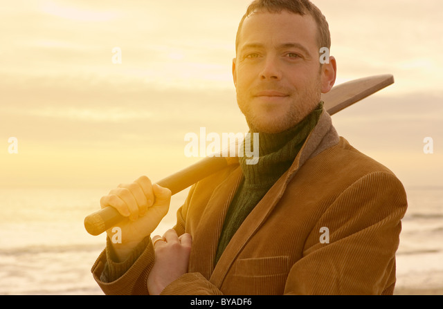 Man on beach with old cricket bat - Stock Image
