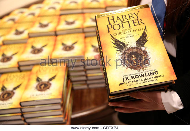 A store assistant holds copies of the book of the play of Harry Potter and the Cursed Child parts One and Two at - Stock-Bilder