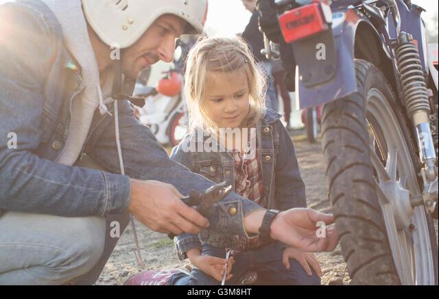 Man fixing wheel on moped, daughter watching - Stock Image