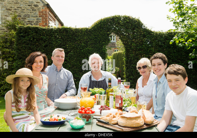 Portrait of three generational family enjoying lunch outdoors - Stock Image