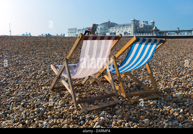 Deckchairs in front of Brighton Pier on the beach - Stock Image