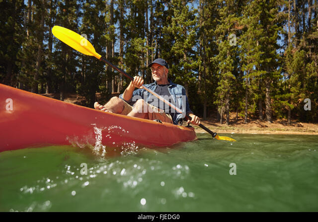 Portrait of mature man paddling a kayak in a lake. Senior caucasian man canoeing on summer day. - Stock Image