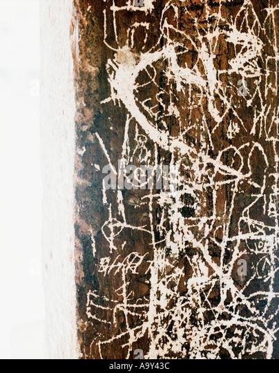 bright white graffiti on brown wall - Stock Image