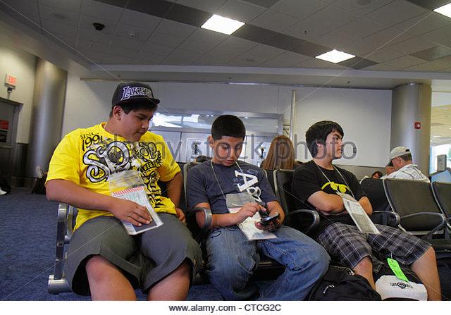 Miami Florida Miami International Airport MIA gate area Hispanic teen adolescent boy passport around neck playing - Stock Image