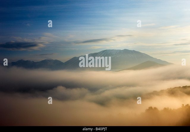 mist lying on the Piano Grande at dawn with the mountains of Monti Sibillini National Park rising above, Umbria, - Stock-Bilder