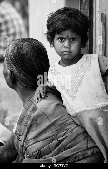 Indian toddler leaning on her grandmother in the doorway of there house in a rural indian village. Monochrome - Stock Image