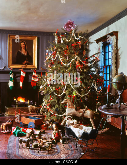 1970s 1980s OLD FASHIONED DECORATED CHRISTMAS TREE WITH POPCORN GARLANDS BY FIREPLACE ANTIQUE TOYS AROUND - Stock Image