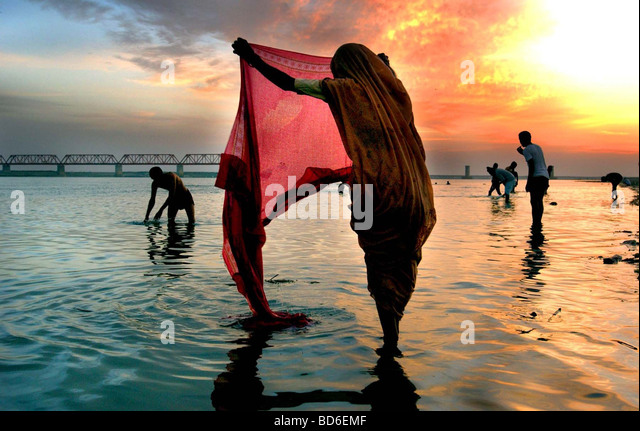 Hindus wash after making prayers to Lord Shiva at the river Saruj in the northern Indian city of Ayodhya at sunrise - Stock Image
