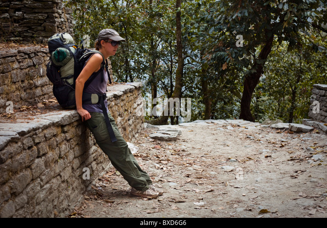 Caucasian female resting at a stone ledge wile trekking in Nepal. - Stock Image