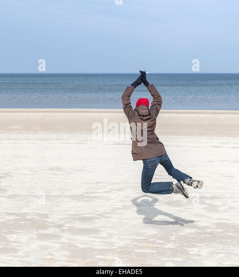 Woman jumping on beach, winter active lifestyle concept, space for text. - Stock Image
