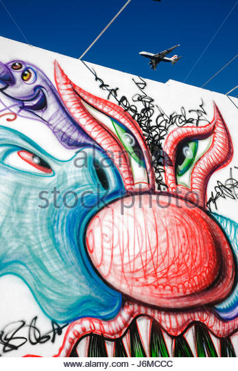 Miami Florida Wynwood Design District mural art painting warehouse wall urban commercial airliner jet plane - Stock Image