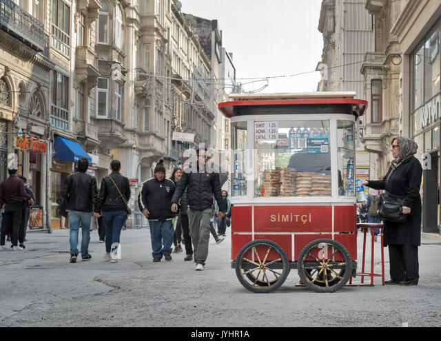 Istanbul, Turkey - April 24, 2017: Old Turkish lady buying fast food meal from a traditional Turkish Simit (Turkish - Stock Image