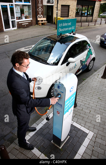 Electric car, powered by an electric motor, using energy, stored in batteries. Fiat 500 model at a pubic charging - Stock Image