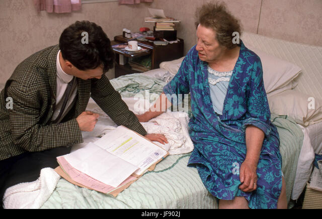 GP on a home visit checking over an old woman in sheltered accommodation - Stock Image