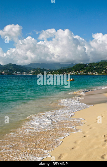 Grenada beach Grand Anse Beach sand and surf waves in foreground capital city of st george's in background - Stock Image