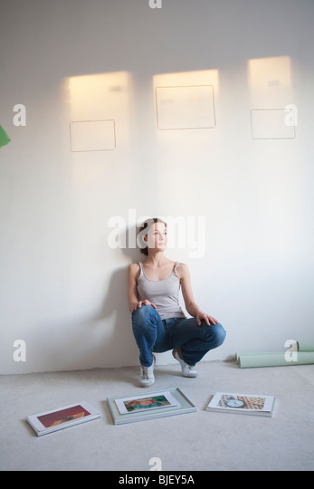 Woman decides on pictures to mount in new apartment - Stock Image
