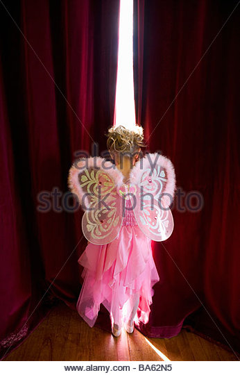 Girl (4-6) with fairy wings looking out gap in curtains, rear view - Stock-Bilder
