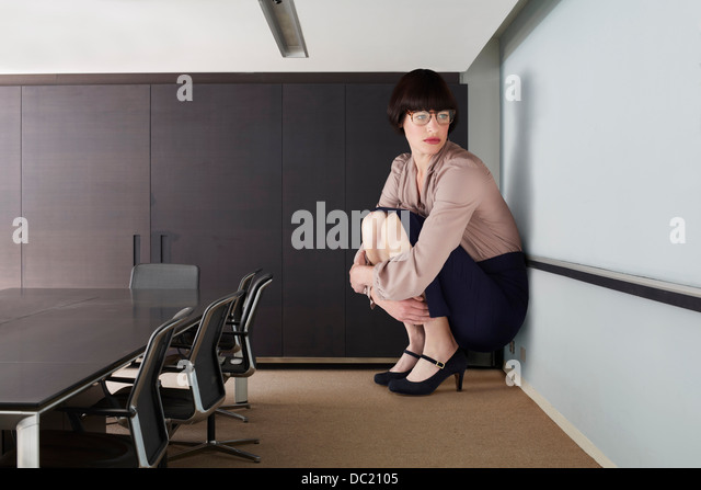 Businesswoman crouching in small conference room - Stock Image