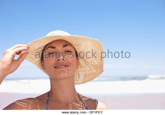 Woman wearing sun hat on beach - Stock Image