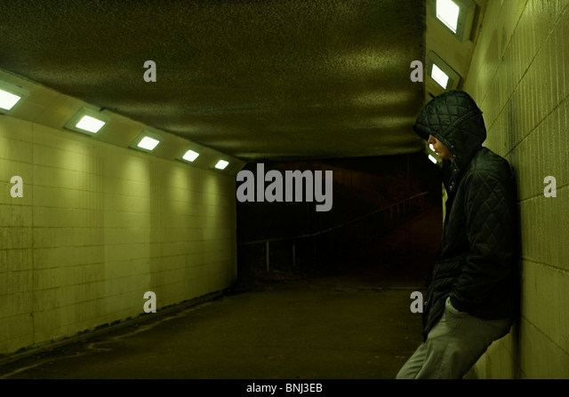 Teenage boy leaning against subway wall at night. - Stock Image