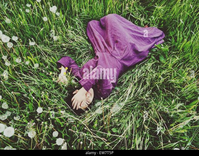 Elevated view of a woman lying in the grass with her hand covering her face - Stock Image