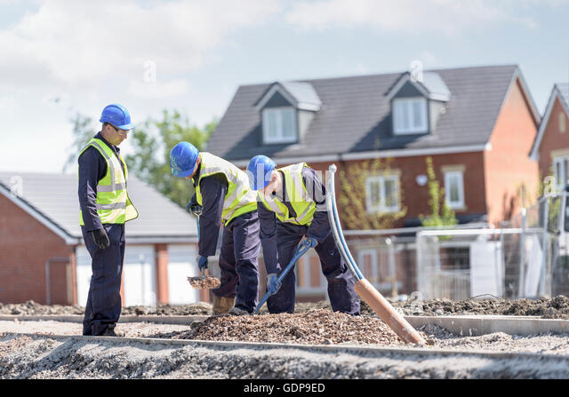 Apprentice builders digging on building site - Stock Image