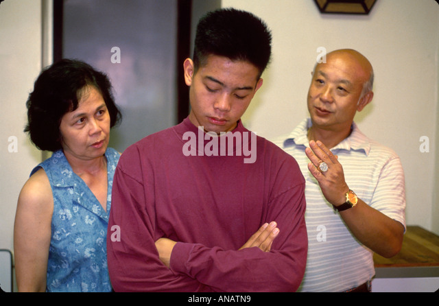 New Jersey Teaneck Asian family parents scold teen son behavior home relationships - Stock Image