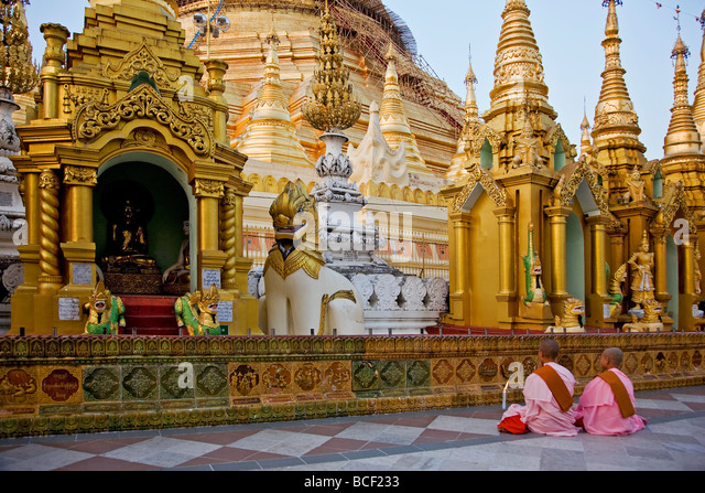 Myanmar, Burma, Yangon. Two young Buddhist nuns pray at the Shwedagon Golden Temple complex. - Stock-Bilder