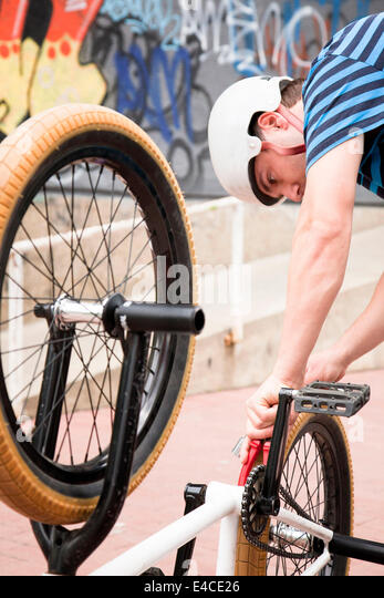Young man with cycling helmet fixing BMX bike - Stock Image