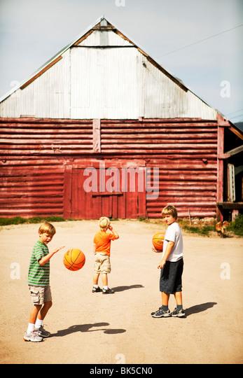 Boys playing basketball near barn - Stock Image