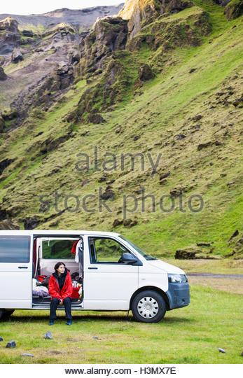 Woman sitting in minivan by mountain, Thakgil, Vik, Iceland - Stock Image