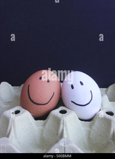 Happy faces, brown and white eggs. - Stock Image