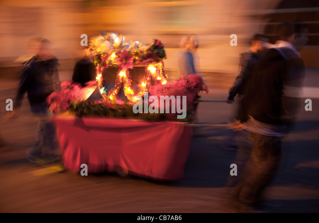 Youths walking around the town's streets with a cart that holds a statue of baby Jesus in Malta. - Stock-Bilder