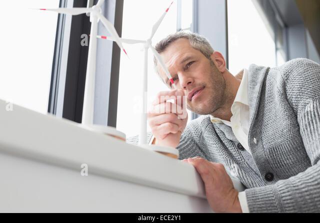 Businessman looking wind turbine - Stock Image