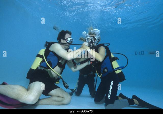 divers practising out of air scenario in swimming pool - Stock Image
