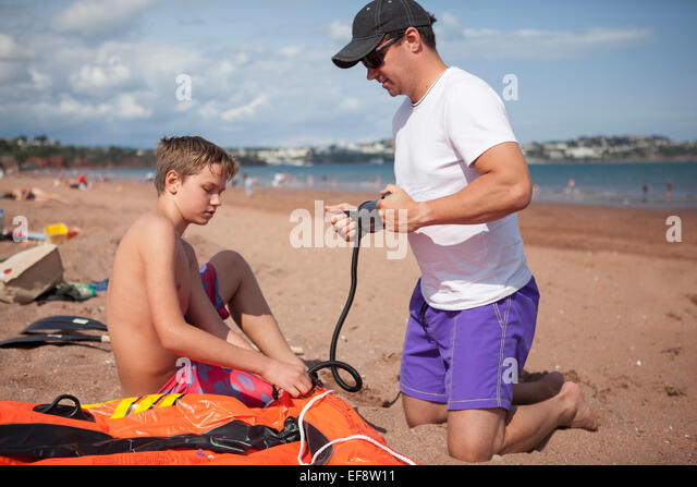 Father and son (12-13) inflating boat on beach - Stock Image