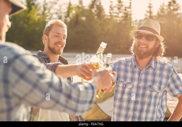 Men making a toast with beer bottles, smiling - Stock Image