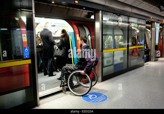 Wheelchair user boarding a London Underground train - Stock Image