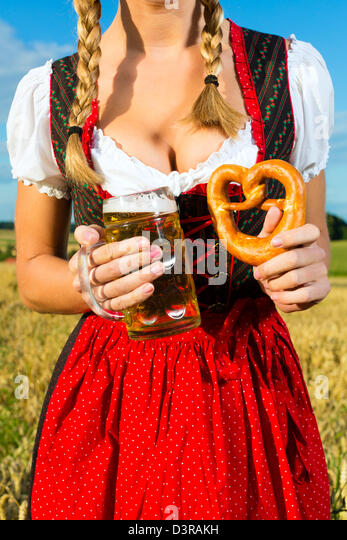 Young Bavarian woman drinking beer and keeping a pretzel in dirndl at meadow - Stock-Bilder