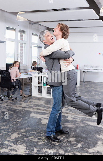 Germany, Bavaria, Munich, Men embracing in office, colleagues working in backgrounds - Stock-Bilder