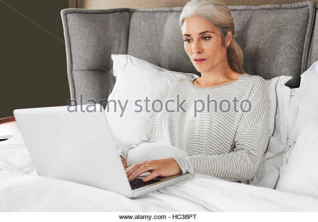 Mature woman using laptop in bed. - Stock Image