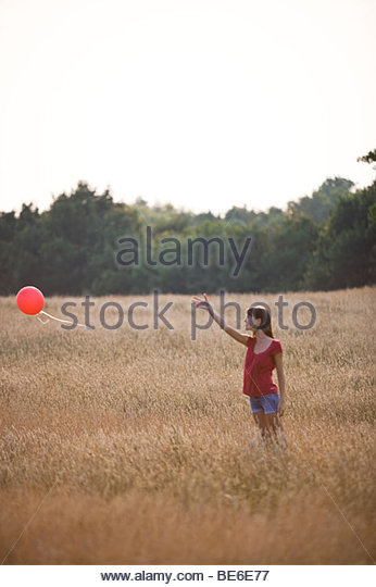 A young woman standing in a field letting go of a red balloon - Stock-Bilder