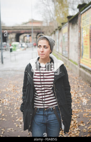 Teenager with headphones on street - Stock Image