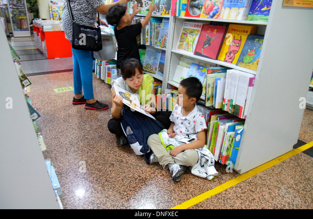 Beijing China Wangfujing Xinhua Bookstore shopping inside sale books shelves Asian woman mother boy son family reading - Stock Image