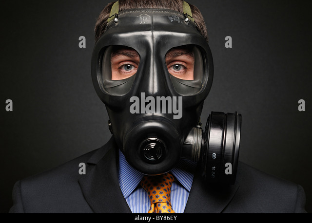 Businessman Wearing Gas Mask - Stock Image