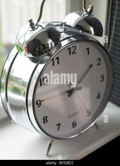 Close-up view of old-fashioned alarm clock on windowsill - Stock Image